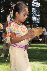 A young Washoe indian girl carries a basket in the Wa She Shu 'It Deh festival at Valhalla
