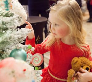 Sweet little girl touches a cupcake ornament on a Christmas tree.