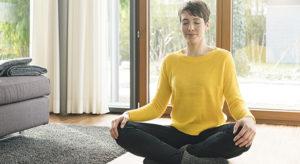 Portrait of woman sitting on the floor of living room floor meditating
