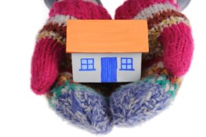 Wool mittens holding a small house